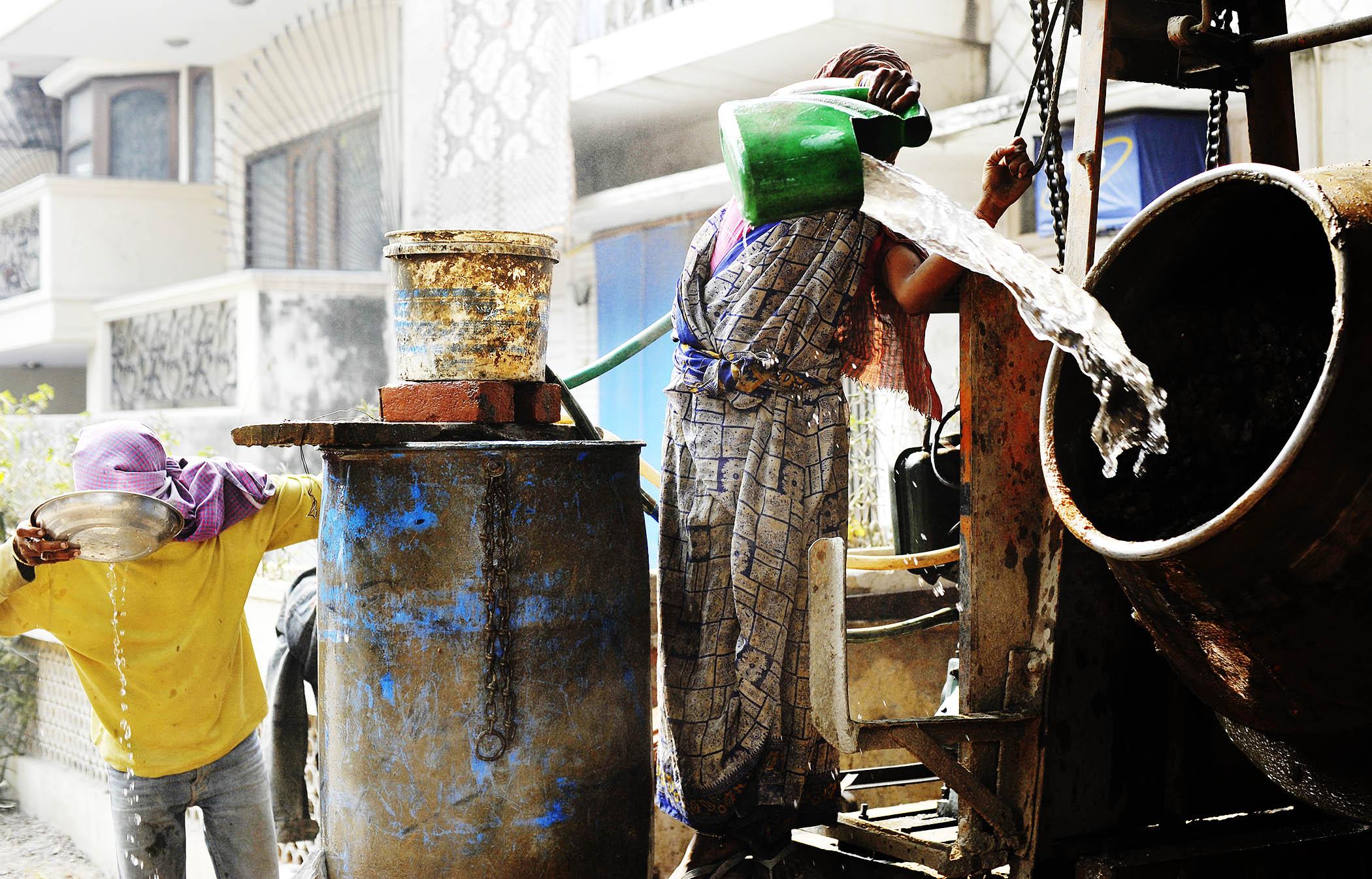 New Dehli, India. Bygningsarbeidere. Heller vann i sementblanderen.